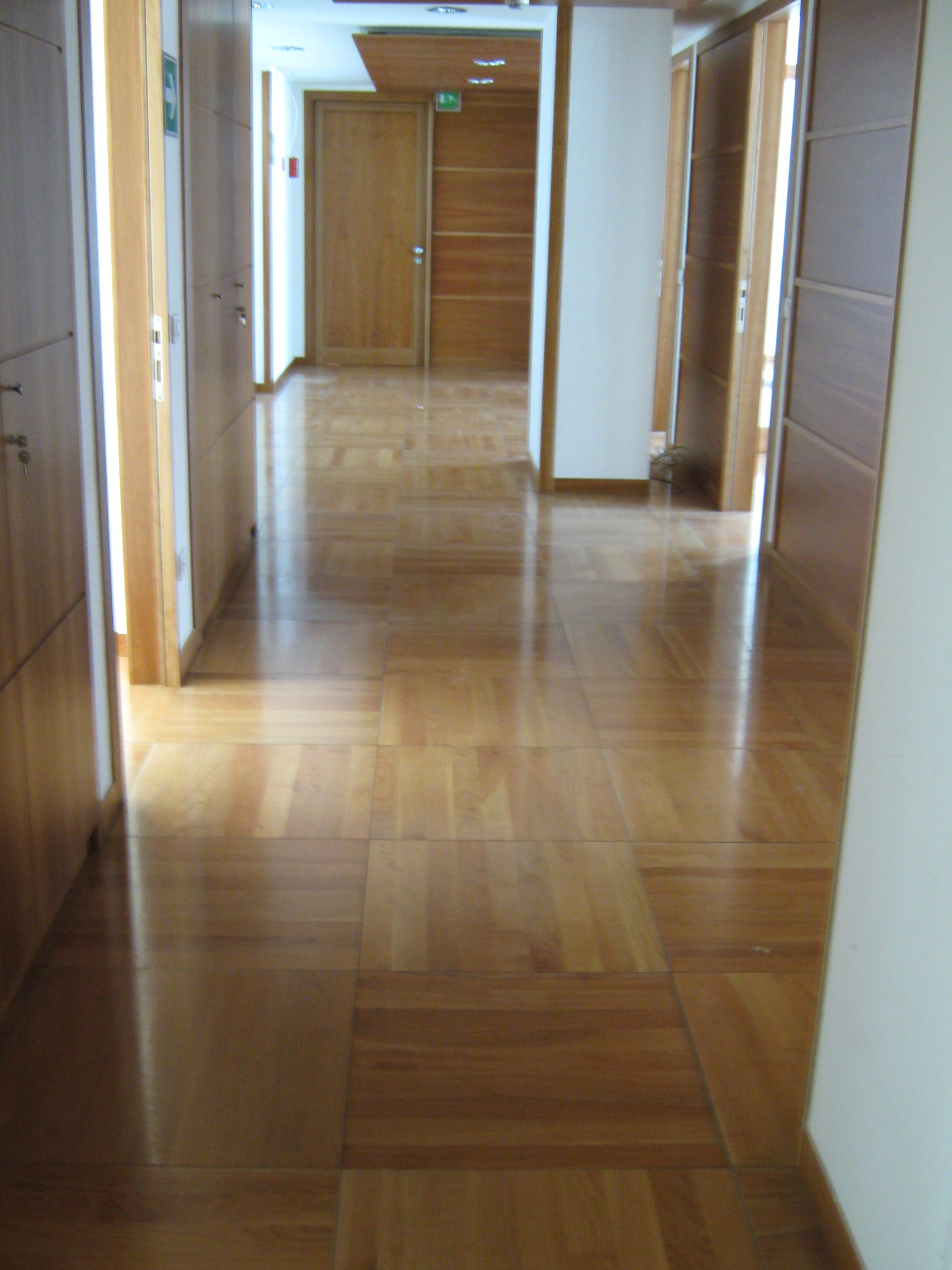 1. Corridoio uffici in parquet di doghe in legno disposte a quadri regolari: stato di fatto.