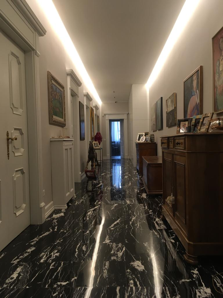 11. Corridoio con pavimento in marmo nero lucidato, soffitto con finitura cornice a gesso e gole luminose, porte con imbotte il legno decorato: lavori ultimati.