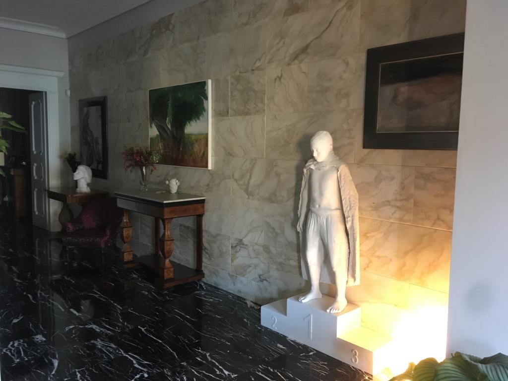12. Scorcio vista corridoio con pavimento in marmo nero lucidato, rivestimento pareti in piastrelle di marmo e arredo in legno d'epoca: lavori ultimati.