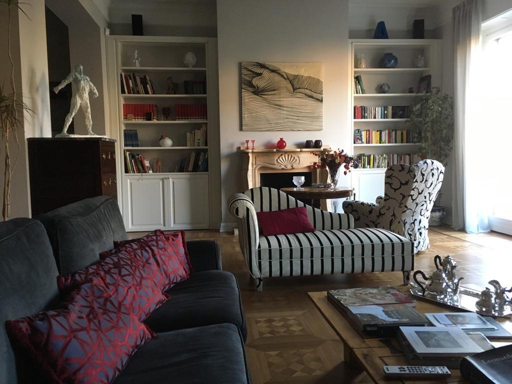 14. Vista salotto con arredi personalizzati, pavimento in parquet a cassettoni lucidato e camino con imbotte decorato: lavori ultimati.