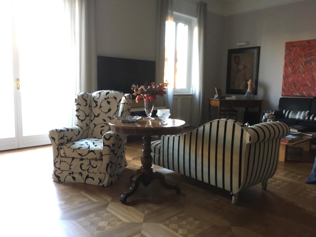 15. Vista salotto con arredi personalizzati, tavolo circolare in legno di fattura artigianale, pavimento in parquet a cassettoni lucidato: lavori ultimati.