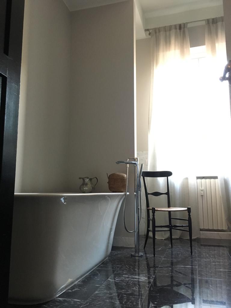 16. Vista bagno con vasca appoggiata su pavimento in marmo nero lucidato e lamato: lavori ultimati.
