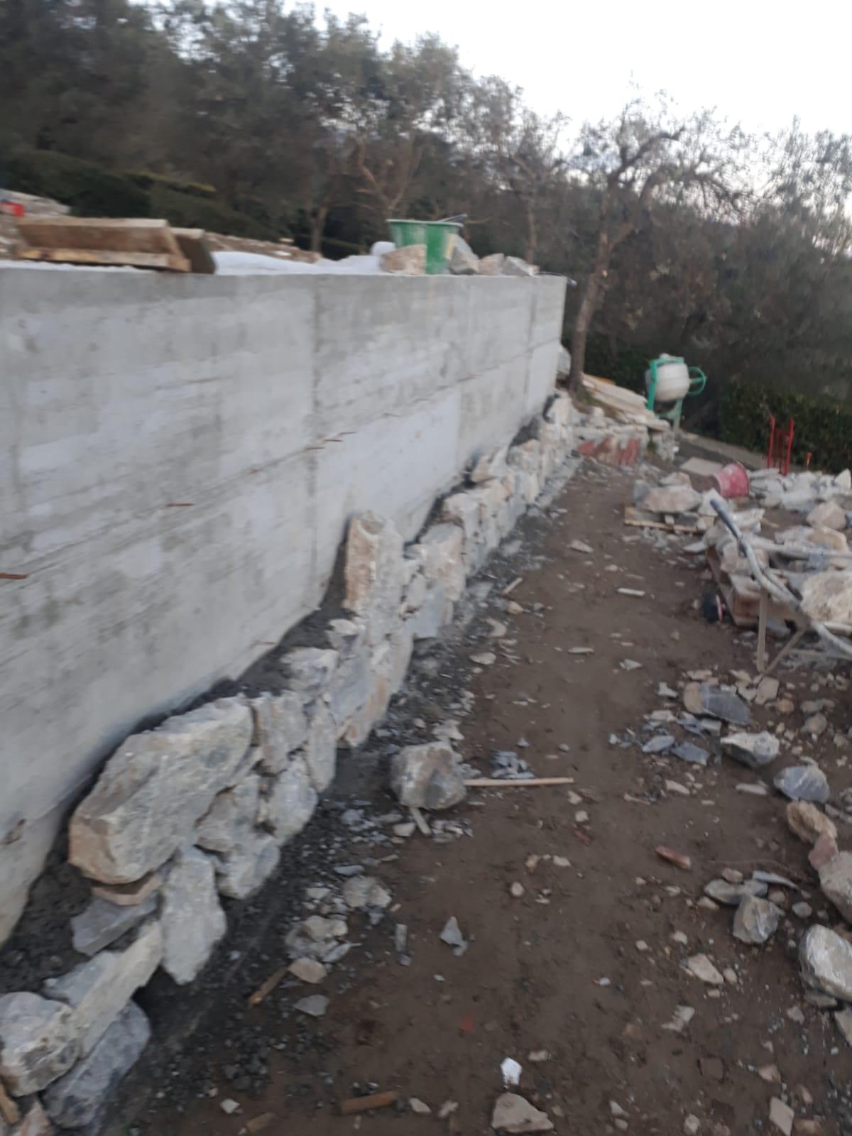 22. Posa del rivestimento dei muri di contenimento con pietra naturale rustica con l'ausilio di malta tra i giunti: lavori in corso.