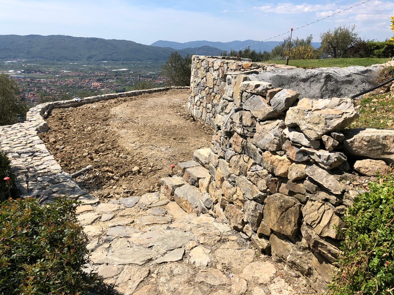 25. Completamento delle opere di finitura dei muri di contenimento rivestite in pietra naturale rustica: lavori ultimati.