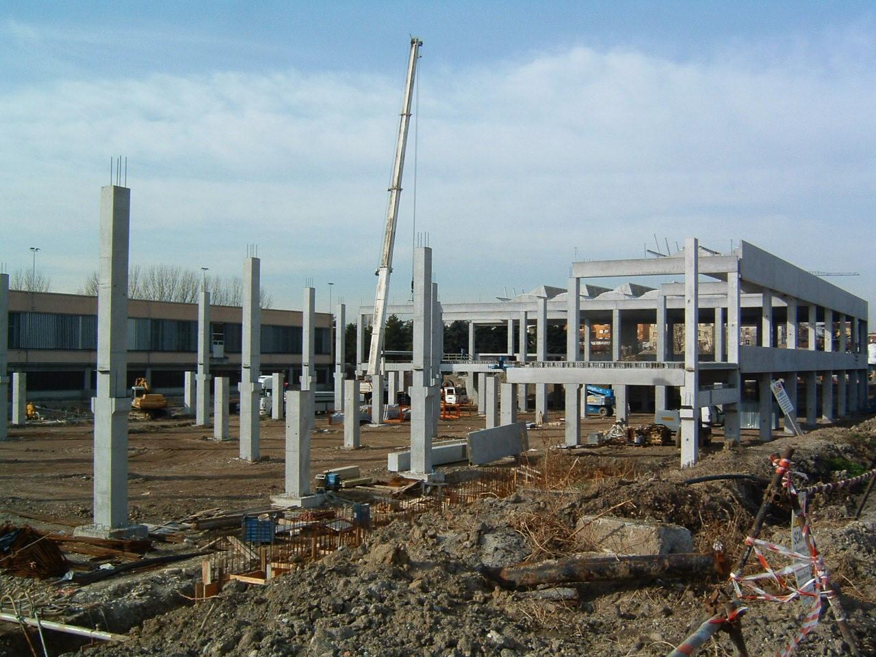 4. Posa di elementi prefabbricati in corso d'opera, con pilastri in c.a. posti su plinti di fondazione e ferri di chiamata: lavori in corso.