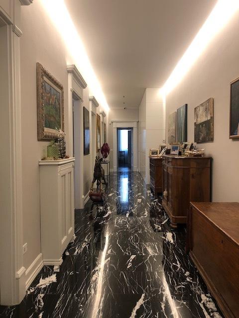 5. Corridoio di servizio con pavimenti in marmo nero lucidato, soffitti con cornici a gesso e gole luminose, pareti rivestite in piastrelle ceramiche e arredi d'epoca in legno: lavori ultimati.