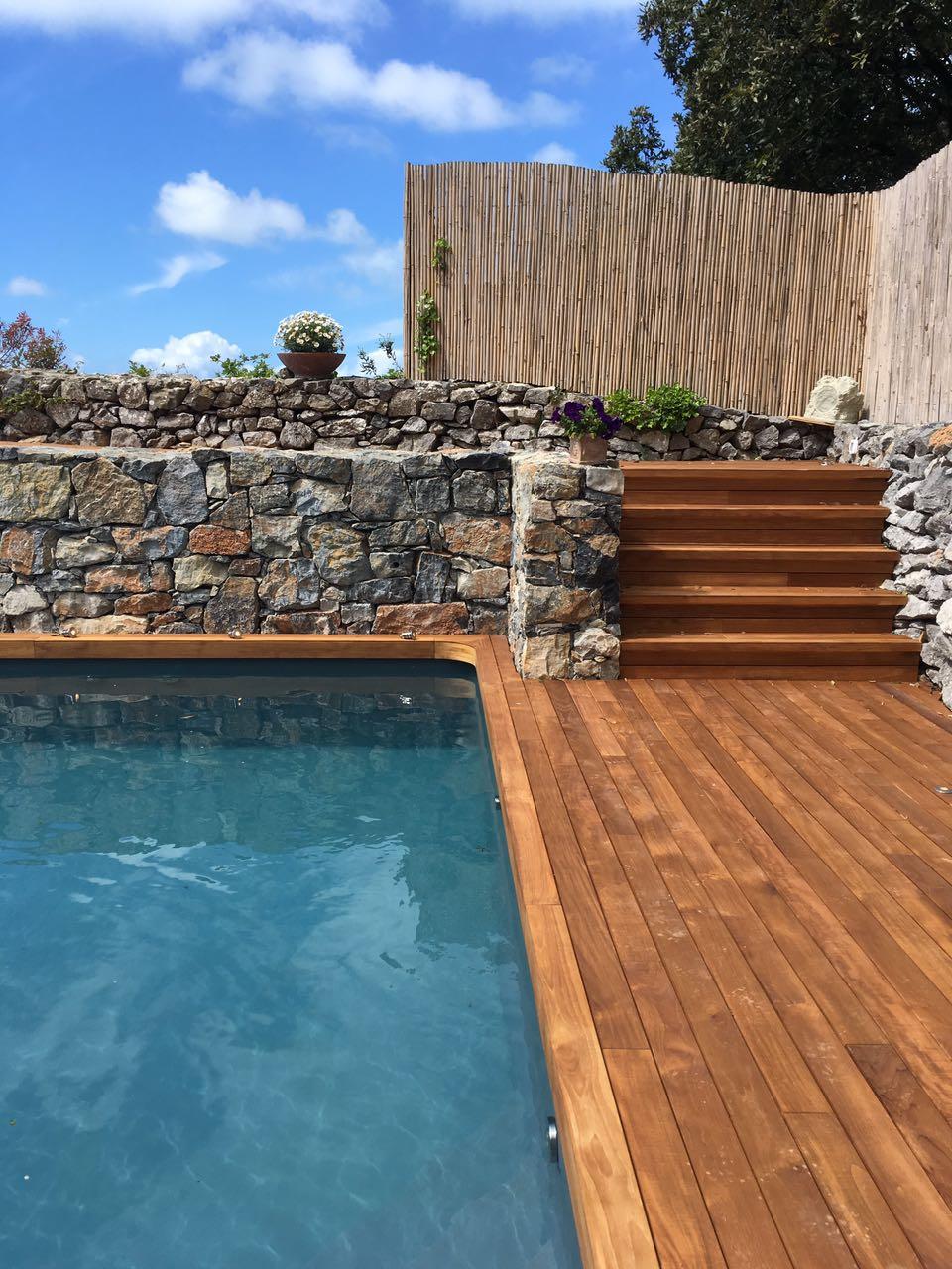 7. Realizzazione piscina interrata scoperta con pavimentazione e gradinate in doghe di legno, parapetto e parete in pietra naturale: lavori ultimati.