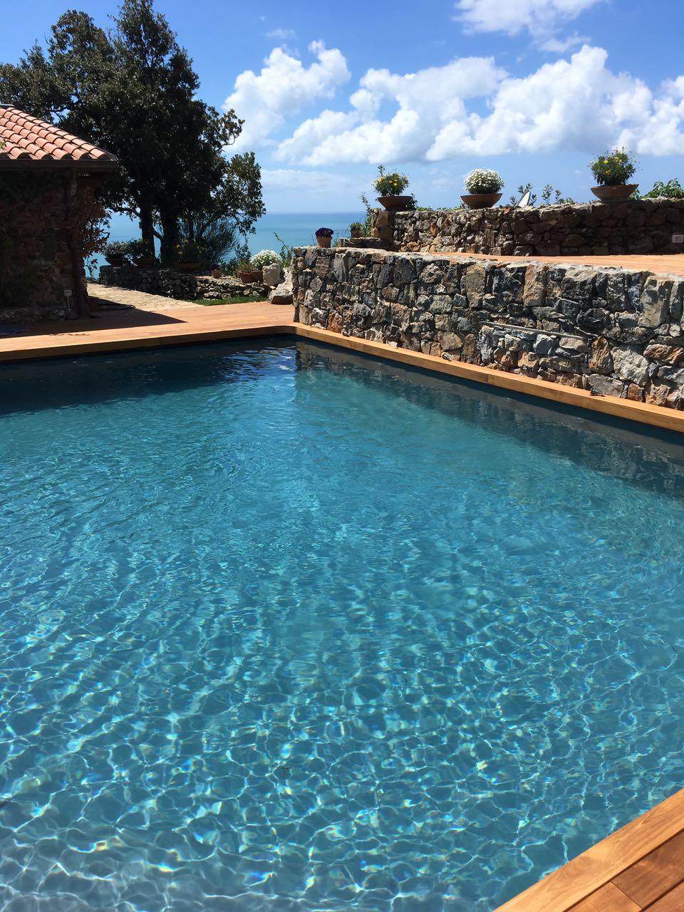 8. Realizzazione piscina interrata scoperta, vista vasca lato mare e muratura in pietra naturale posata rustica: lavori ultimati.