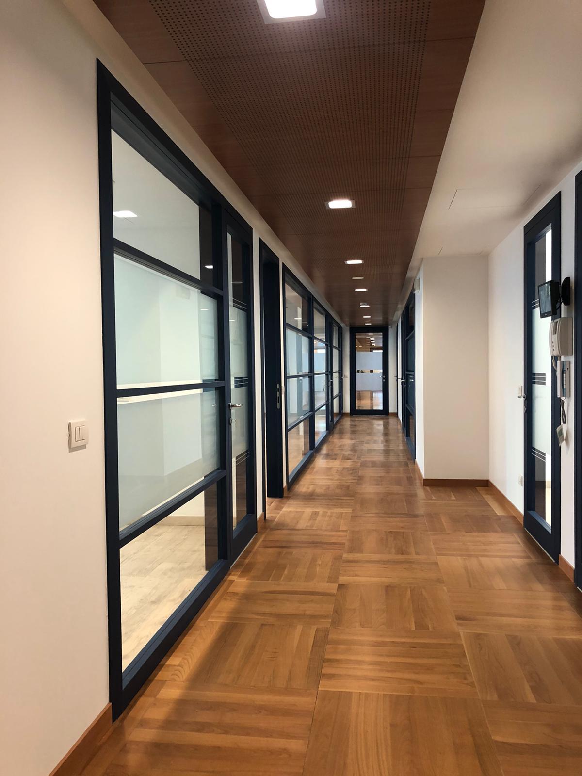 1. Corridoio uffici in parquet di legno posati a cassettoni regolari, illuminazione led a soffitto e porte vetrate satinate: lavori ultimati.