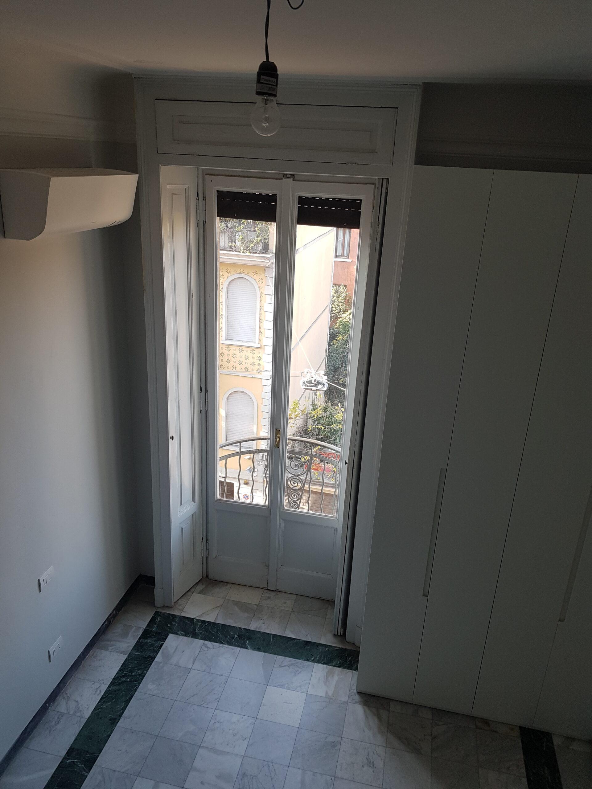 1. Particolare porta finestra con imbotte in legno laccato, pavimento in piastrelle di marmo con perimetro in lastre di marmo nero e illuminazione a soffitto: lavori in corso.