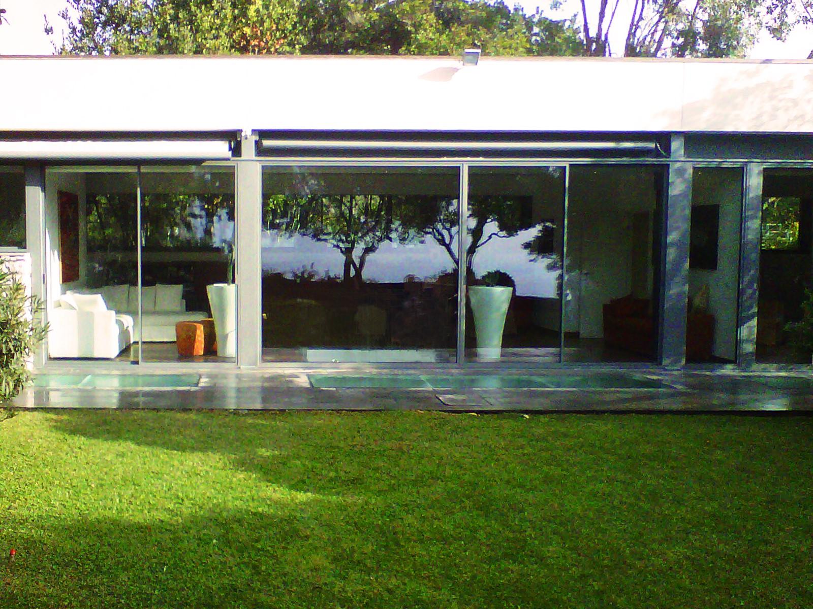 10. Vista esterna villa con pareti vetrate ultimate e particolare di camminamento esterno con vetro stratificato: lavori ultimati.