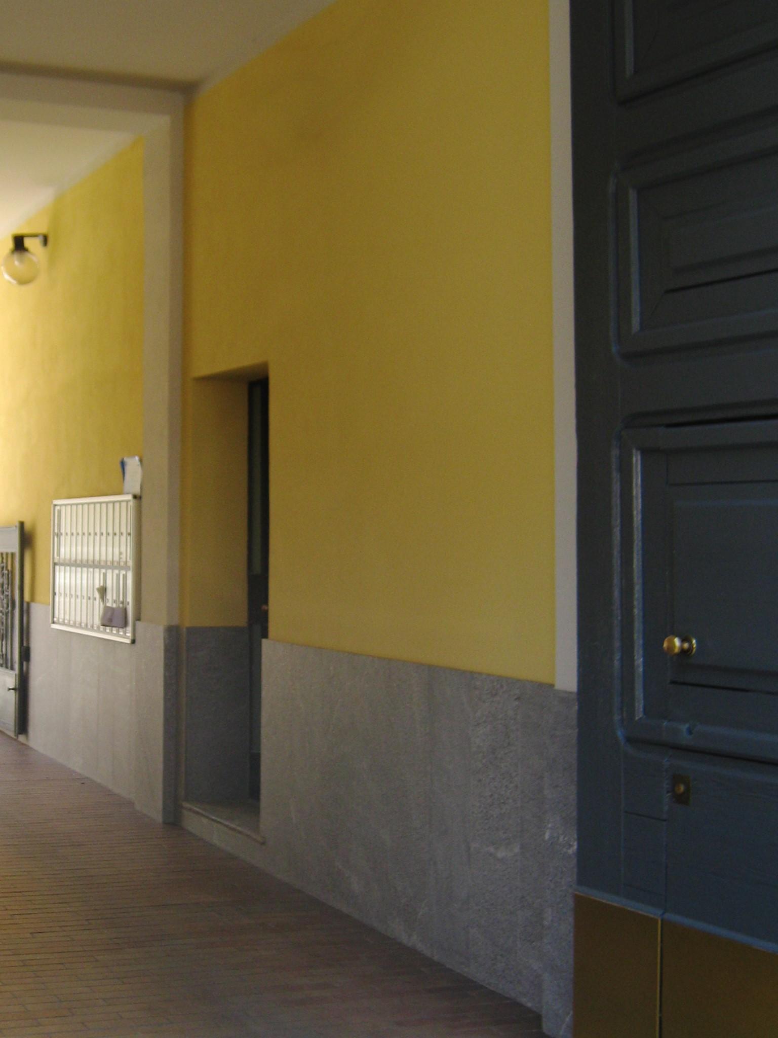11. Atrio con basamento in lastre di marmo Beola grigio scuro, nuovi intonaci e pitture: lavori ultimati.