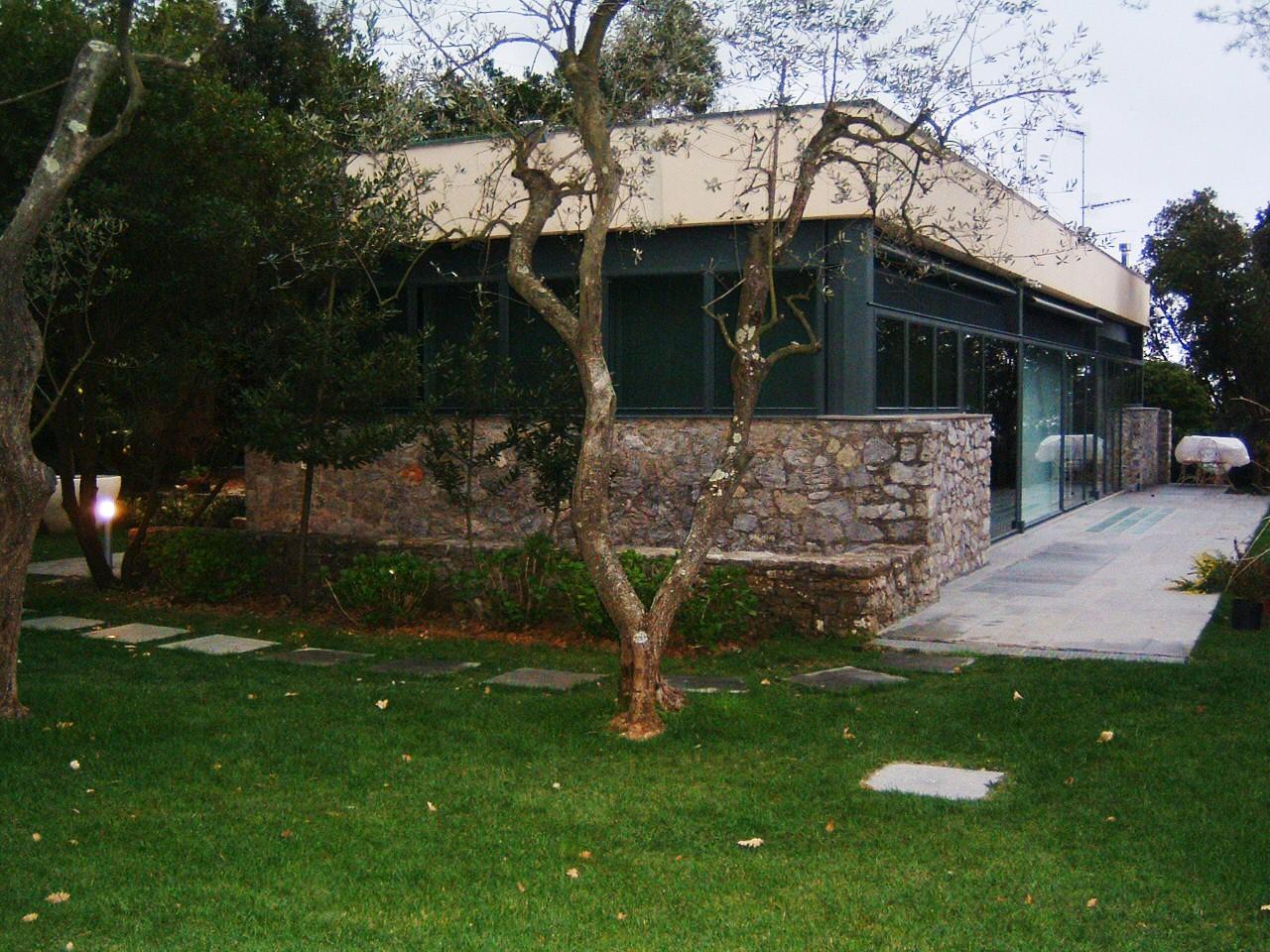 12. Vista esterna della villa dal giardino, con prospetto lato corto composto di serramenti a nastro e basamento rivestito in pietra naturale: lavori ultimati.