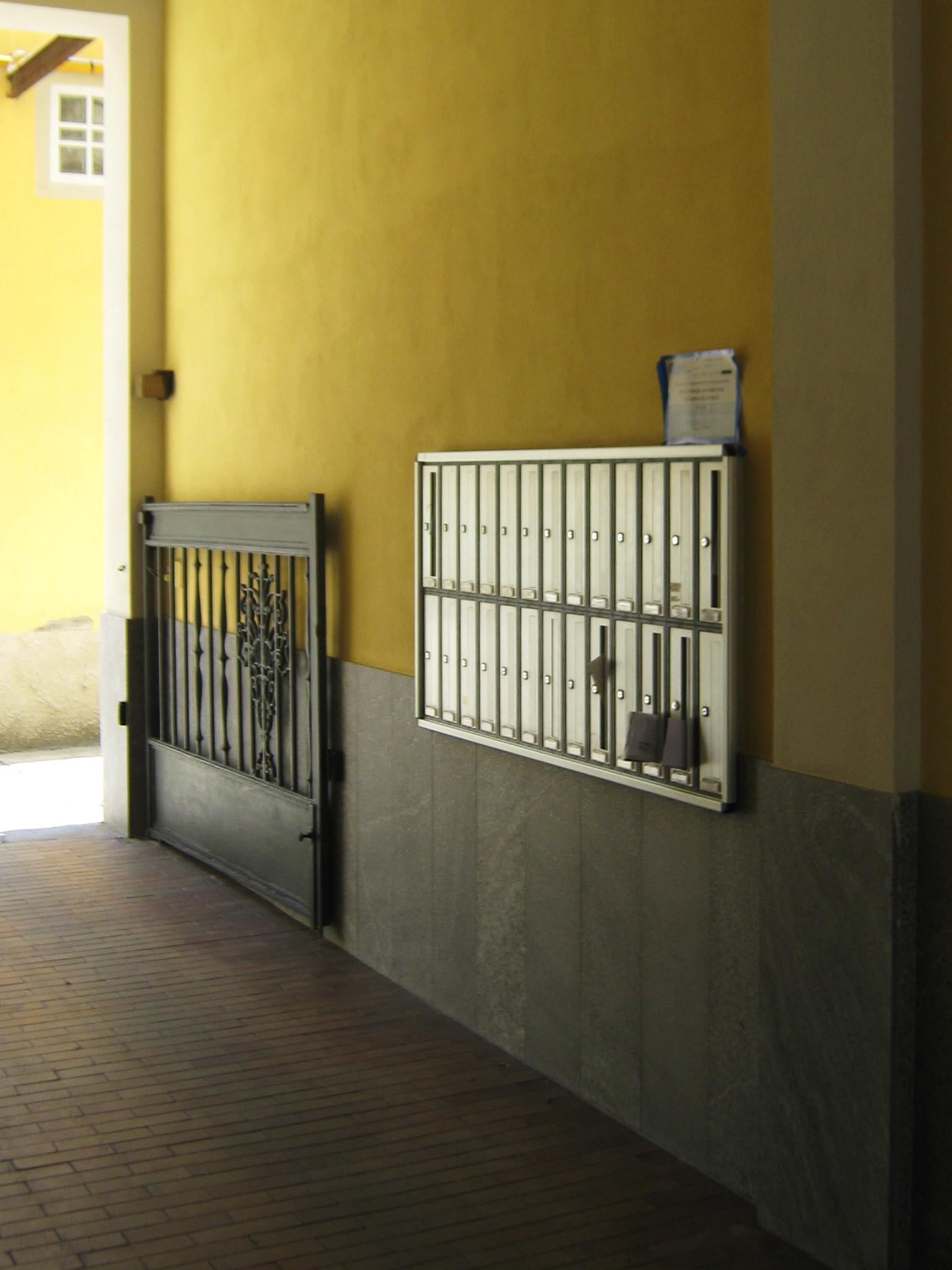 12. Atrio con basamento in lastre di marmo Beola grigio scuro, nuovi intonaci e pitture, vista lato casellario: lavori ultimati.