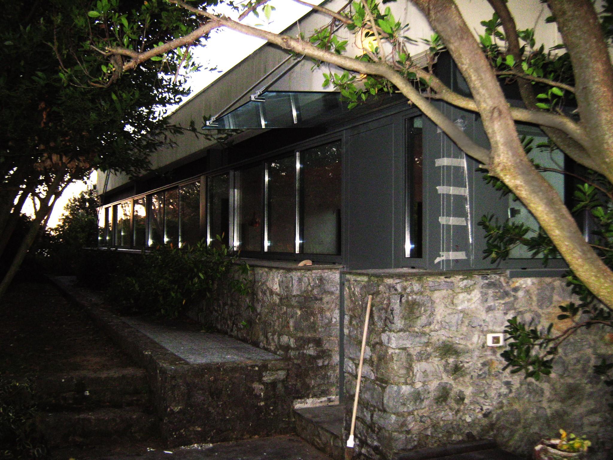 13. Vista di scorcio al crepuscolo serale della villa, lato serramenti a nastro e ingresso protetto da pensilina in vetro e tiranti in acciaio: lavori ultimati.