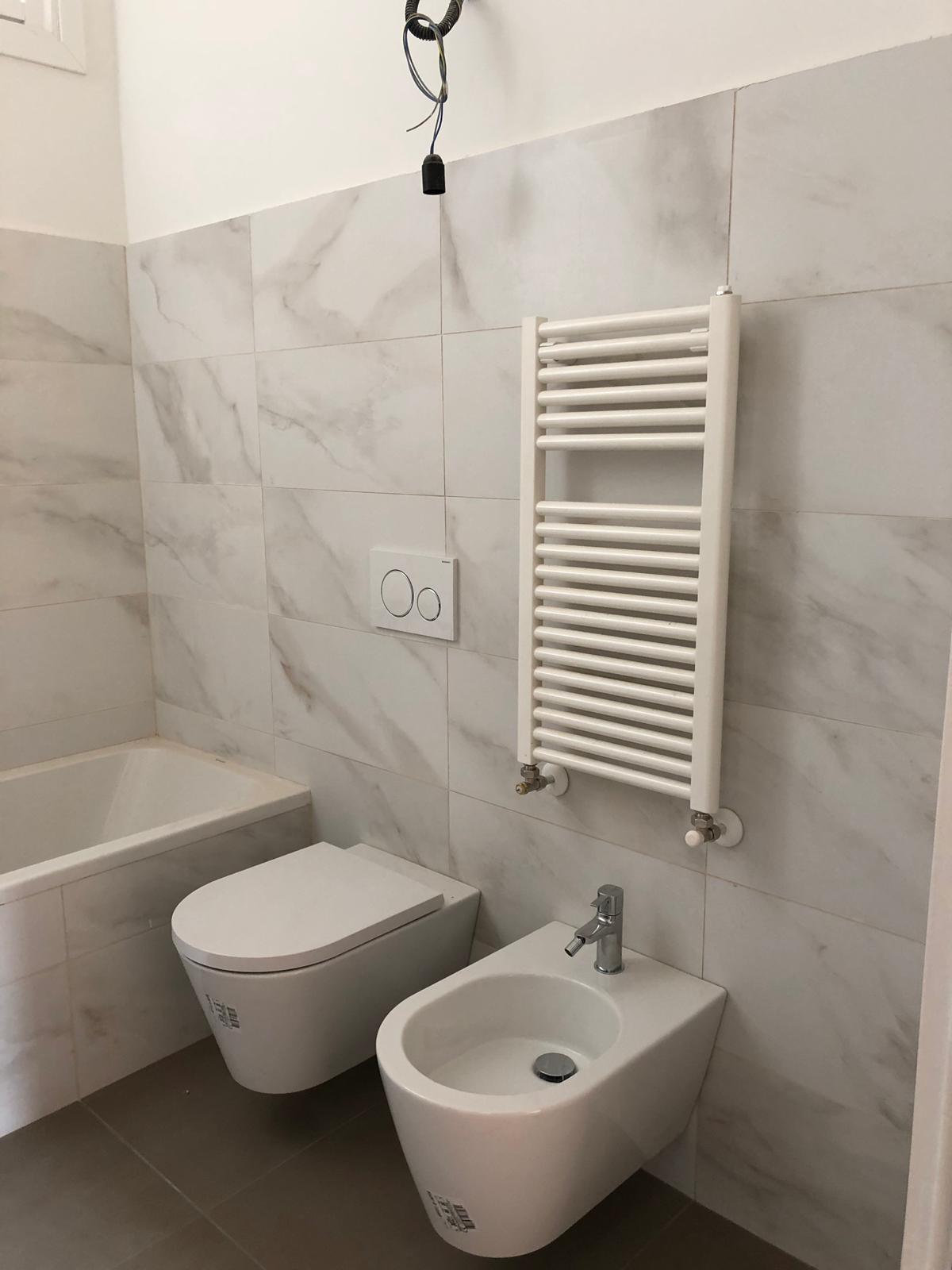 13. Particolare sanitari a parete con scalda salviette in asse, rivestimento pareti e vasca da bagno in lastre di marmo color tortora: lavori in corso.