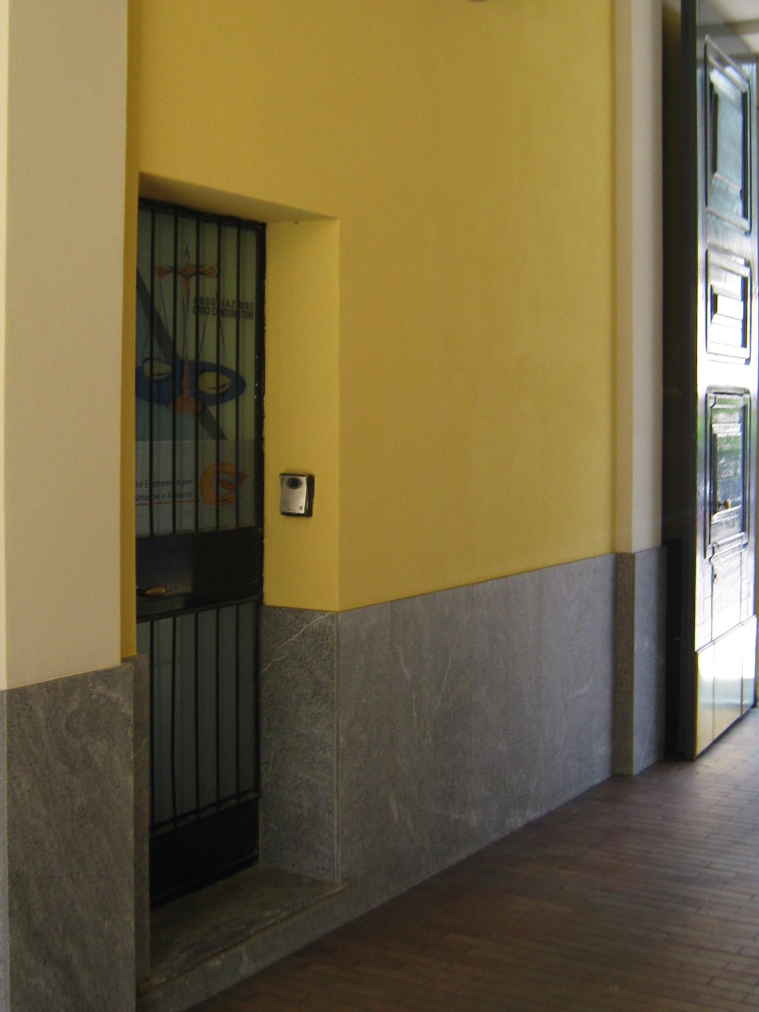 14. Atrio con basamento in lastre di marmo Beola grigio scuro, nuovi intonaci e pitture, vista lato porta di ingresso con citofono: lavori ultimati.
