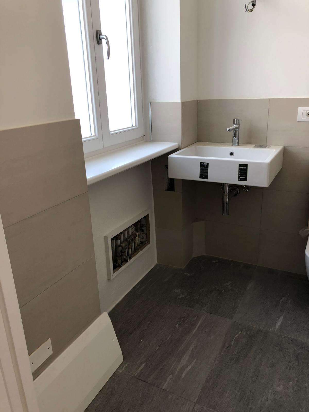 14. Particolare di lavabo sospeso a parete, serramenti in vetrocamera e legno laccato, rivestimento pareti in piastrelle ceramiche e pavimenti in lastre di marmo: lavori in corso.