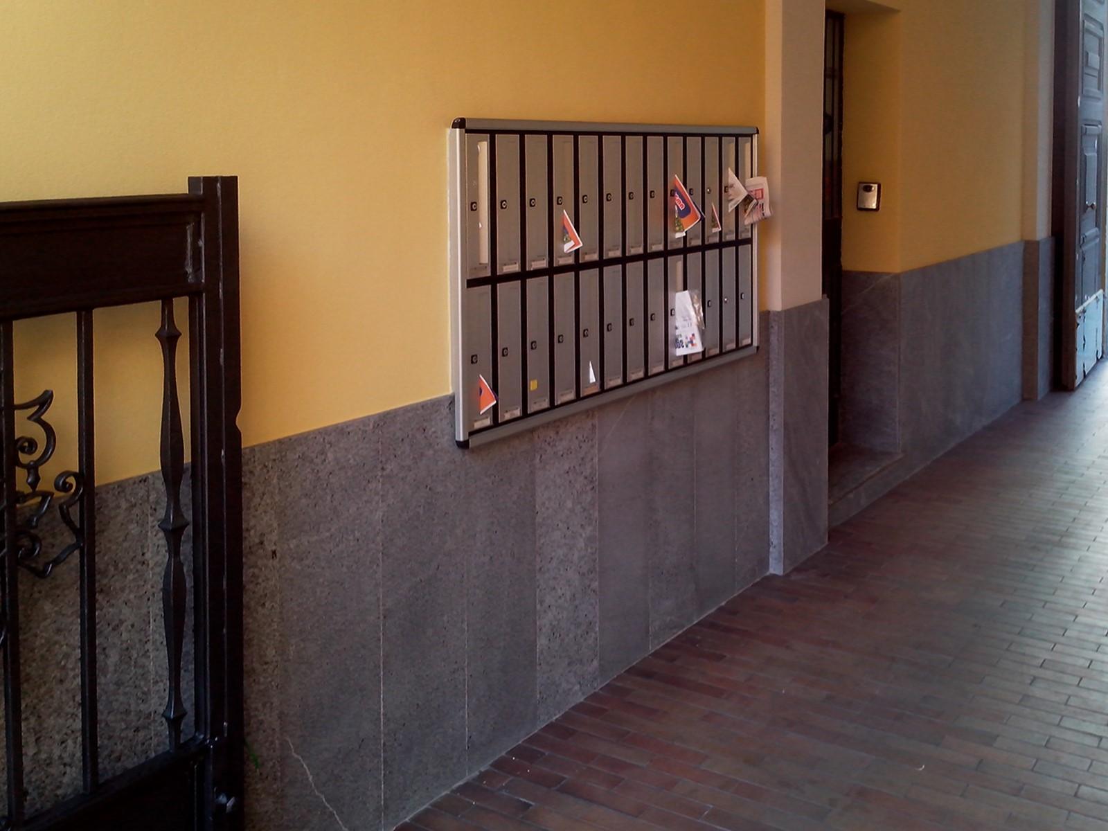 16. Atrio con basamento in lastre di marmo Beola grigio scuro, nuovi intonaci e pitture, vista lato casellario postale: lavori ultimati.