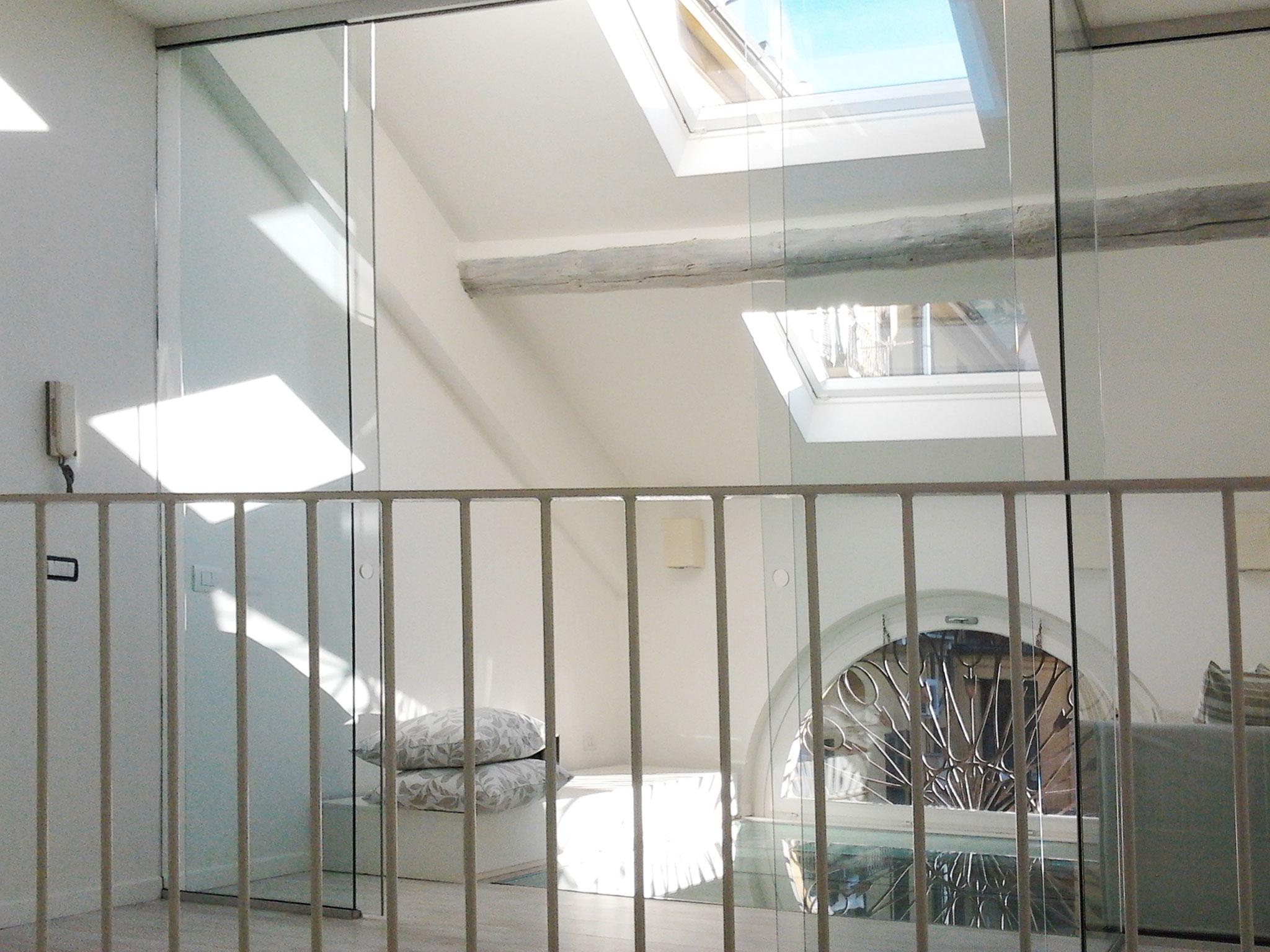 3. Mansarda ambiente studio con divisorio in lastre di vetro ad ante scorrevoli, ringhiera di protezione in metallo e pavimento calpestabile con vetro stratificato: lavori ultimati.