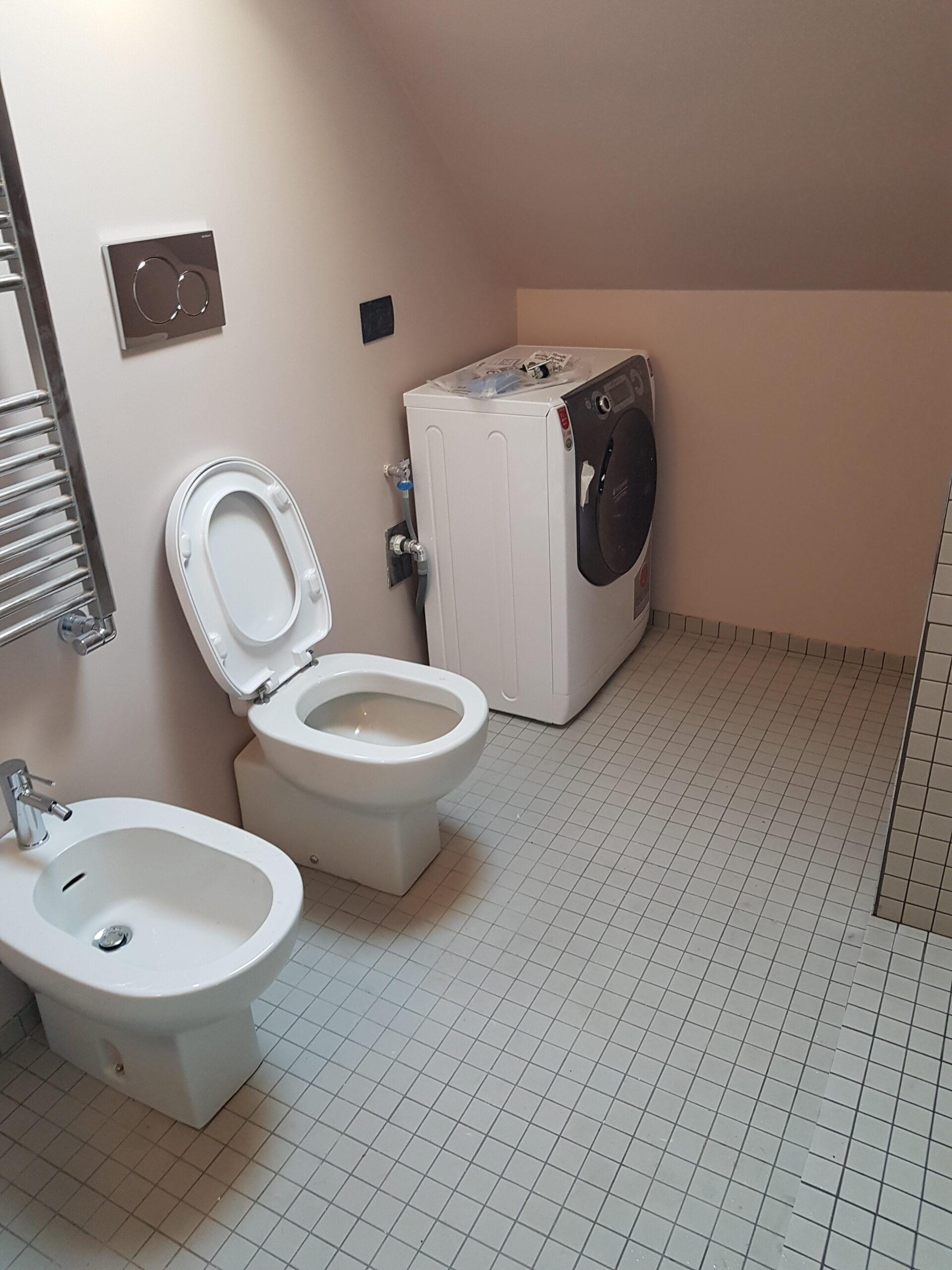 3. Vista locale bagno con sanitari bianchi ceramici, soffitto inclinato a falda e pavimento in piastrelle ceramiche a quadri: lavori in corso.