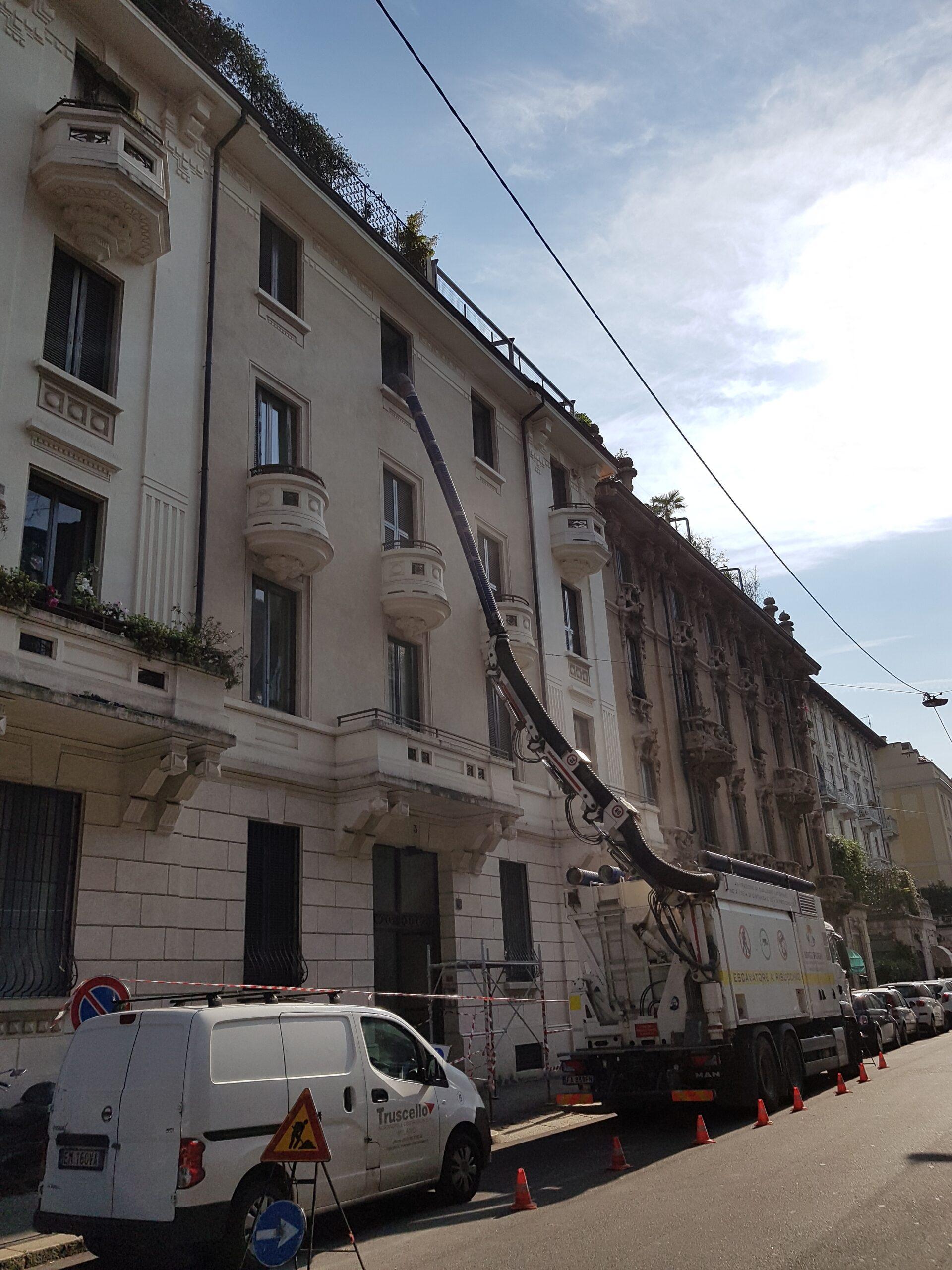 4. Escavatore a risucchio posizionato al lato strada e collegato al piano demolizioni di alloggio in Via Donatello: lavori in corso.