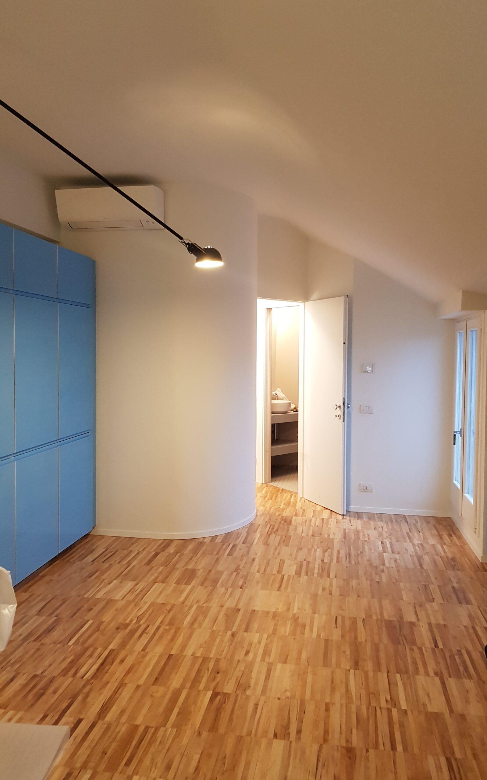 5. Locale alloggio con pavimento in doghe di legno, porta finestra con imbotte in legno laccato e soffitto inclinato a falda: lavori ultimati.