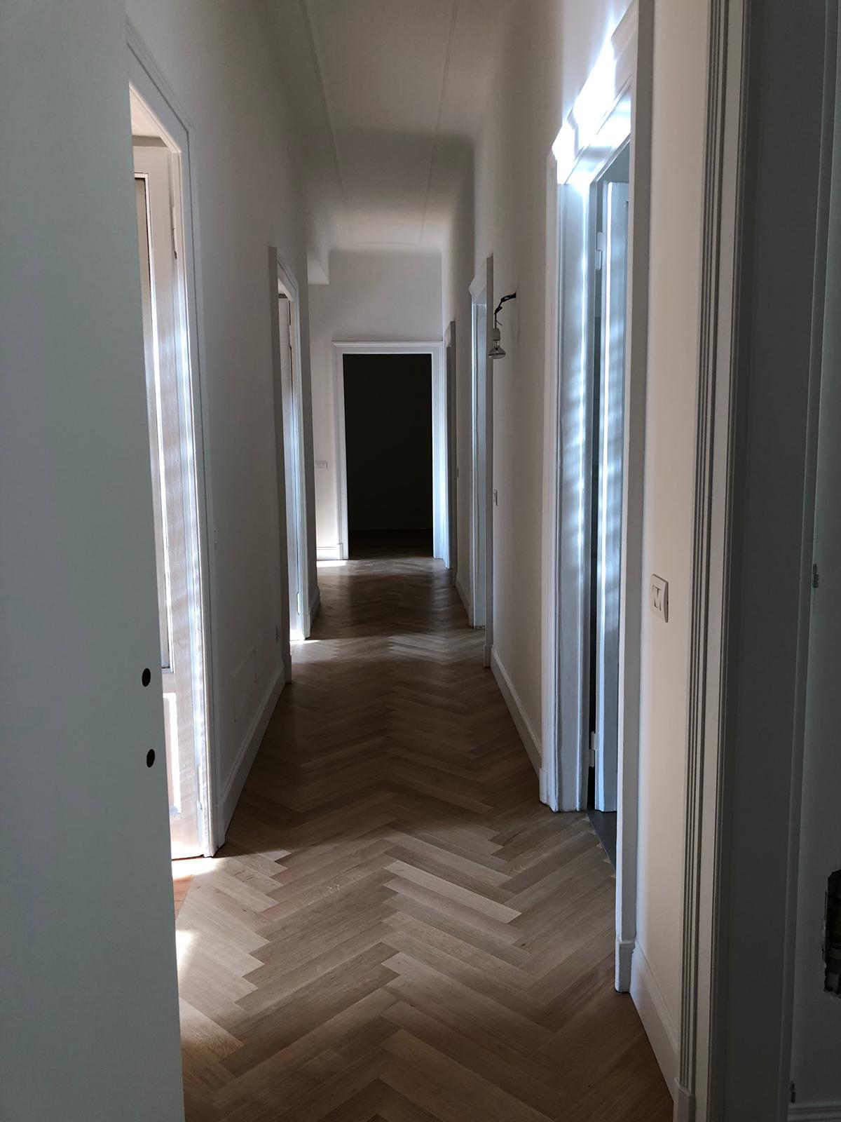 7. Corridoio con pavimento in parquet in doghe di legno disposte a spina di pesce all'italiana e porte con imbotti in legno laccato: lavori in corso.