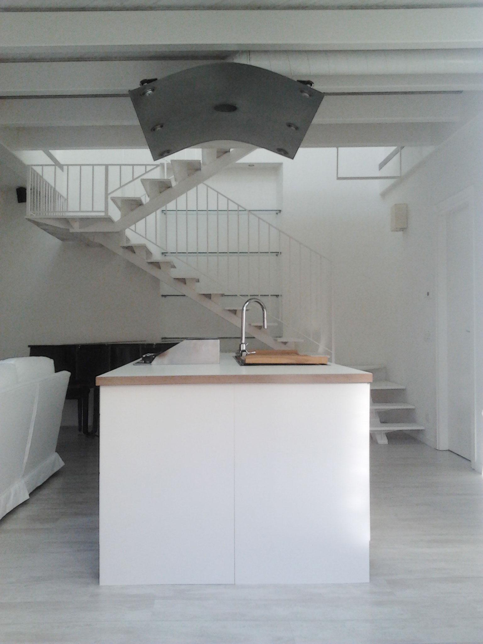 8. Cucina con arredo ad isola, illuminazione di design a sospensione e scala a sbalzo in acciaio: lavori ultimati.