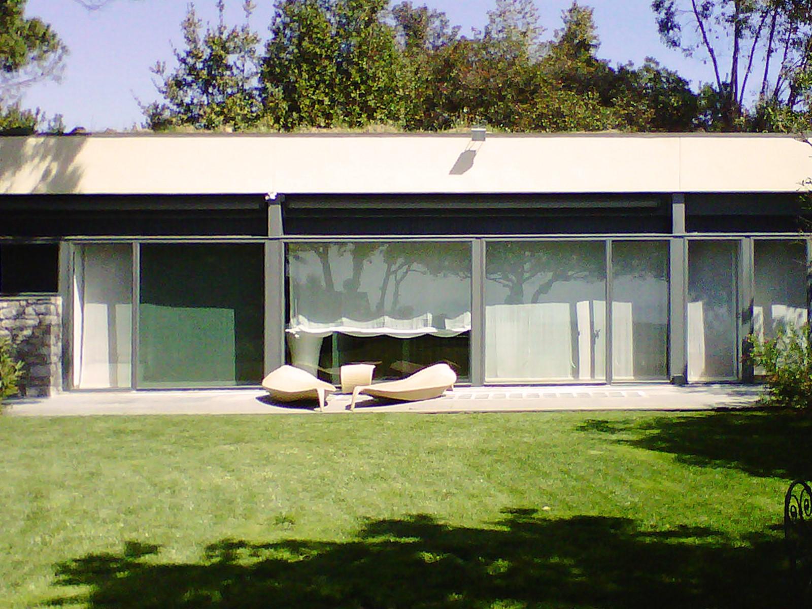 9. Prospetto villa con pareti vetrate ultimate e completa di arredi esterni da giardino: lavori ultimati.